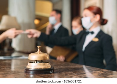 Check in hotel. receptionist at counter in hotel wearing medical masks as precaution against virus. Young woman on a business trip doing check-in at the hotel - Shutterstock ID 1836531721