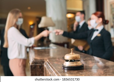 Check in hotel. receptionist at counter in hotel wearing medical masks as precaution against virus. Young woman on a business trip doing check-in at the hotel - Shutterstock ID 1836531730