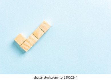 Check mark made with wooden block toys on blue background with copy space to the right. Tick symbol. Satisfaction, ok concept