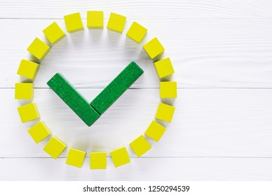 Check mark in round sign from wooden blocks on the white wooden background. Check list button icon.