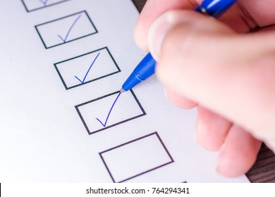 Check off the tasks of a To Do list with a pen