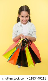 Check out her shopping packages. Child cute shopaholic with bunch shopping bags black friday total sale. Take shopping packages. Girl carries shopping bags yellow background.