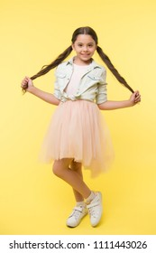 Check out my style. Kid girl charming ponytail hairstyle cute happy yellow background. Child fashionable outfit skirt and denim jacket. Kid stylish fashionable posing holds her long curly hair.