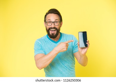 Check out new app. Guy eyeglasses cheerful pointing at smartphone. Man happy user recommends try application for smartphone. Man takes advantages online communication. Guy bearded smartphone user.