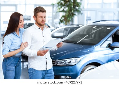 Check put the characteristics. Young handsome man reading an advertising booklet at the car dealership while his beautiful wife embracing him and peeking over his shoulder