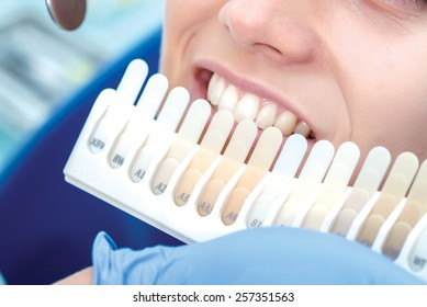 Check and select the color of the teeth in the dentist chair. Dentist makes the process of treatment of a beautiful young girl.