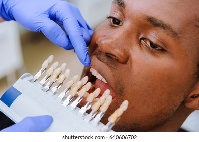 Check and select the color of the teeth. Dentist makes the process of treatment in dental clinic.