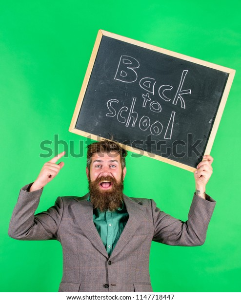 Check this out. Back to school special offer. Man bearded teacher holds blackboard back to school inscription on green background. Special offer discount and sale school season. Offer for pupils.
