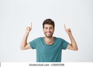 Check this out Cropped studio shot of attractive good-looking excited young man in blue t-shirt pointing fingers up having surprised look, with cheerful and happy expression of face. Broadley smiling.