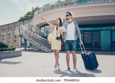 Check this out! Happy married couple are on honey moon, in caps, eyewear and with camera, valises, outdoors, walking on nice spring day