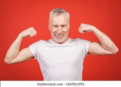 Check this out! Senior man showing muscle. Aged man flexing his arms isolated against red background. Cheerful excited modern cool pensioner grandpa practising bodybuilding.