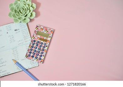 Checkbook Register, Calculator, and Plant on Light Pink Background