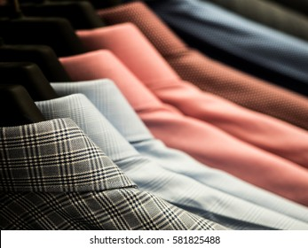 Checked men's shirts hanging on rack.
