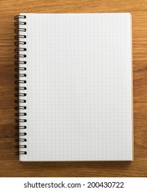 checked notebook on wood background
