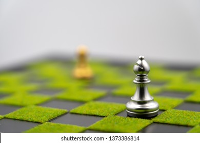 checkerboard background of green grass with bishop. Have copy space. one bishop cna make strong business. Strong leader
