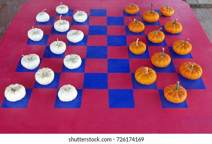 Checkerboard painted on a table with white and orange mini pumpkins as pieces