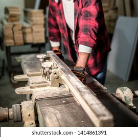 checkerd shirt carpenter using sawmill on the table with safety gloves at his workbench around lots of woods