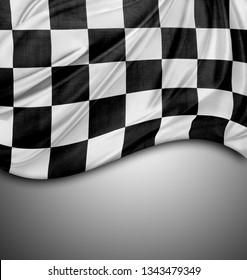 Checkered black and white flag on grey background. Copy space