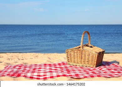 Checkered blanket with picnic basket on sunny beach. Space for text