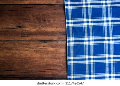Checkered blue napkin on an old wooden brown background, top view. Image with copy space. Kitchen table with a towel - top view with copy space.