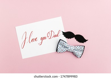 Checkered bow tie and cardboard men's mustache on a pink background. Card with handwritten phrase I love you Dad. Happy Father's Day. Horizontal flat lay, top view.