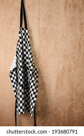 A checkered chef's apron hangs from a rusty nail on an old rendered wall