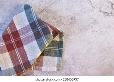 A checkered cloth napkin is placed casually on a marble table or counter.