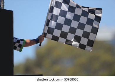 A checkered flag being waved on a raceway.