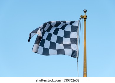 Checkered Flag blowing in wind on a flag pole