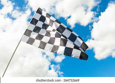 Checkered flag with cumulus clouds behind it