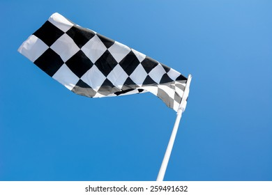 Checkered flag flying on blue sky background
