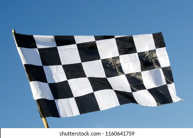 Checkered flag isolated on blue sky background. Copy space