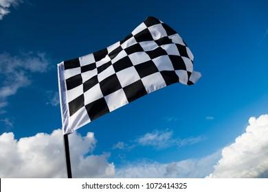 Checkered flag on blue sky