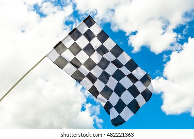 Checkered flag on flagpole waving in the wind with clouds on background