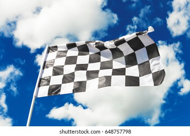 Checkered flag waving with blue sky and clouds behind it. Filtered image: cross processed vintage effect.