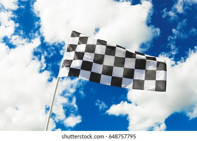 Checkered flag waving in the wind with clouds on background - outdoors shoot. Filtered image: cross processed vintage effect.