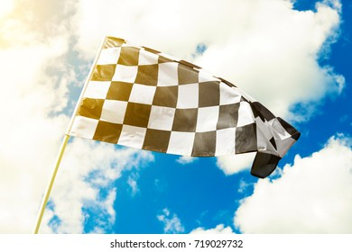 Checkered flag waving in the wind with sun flare visible