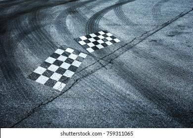 Checkered flags painted on race asphalt road with crossing of tires tracks.