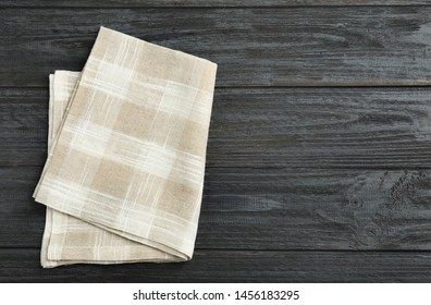 Checkered kitchen towel on black wooden table, top view. Space for text