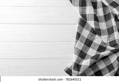 Checkered kitchen towel on white wooden table