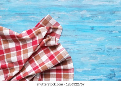 Checkered napkin on blue background top view with copy space