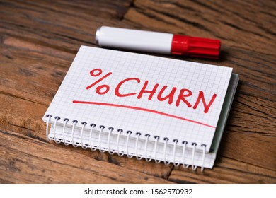 Checkered Notepad With Churn Percent Text Near Red Marker Over Wooden Desk