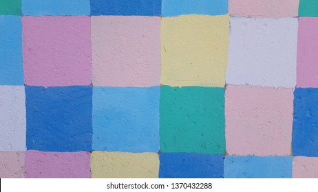 Checkered painted metal surface closeup with uneven colorful squares. Old cracked structure of pastel color painted gates in Odessa city of Ukraine. Abstract background. Grunge backdrop