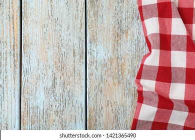 Checkered picnic blanket on wooden background, top view. Space for text