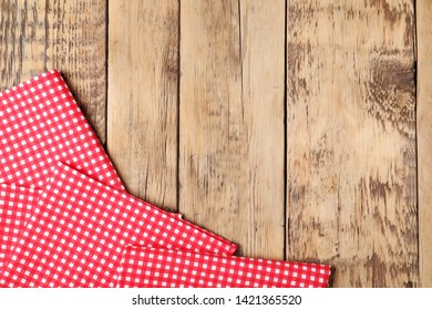 Checkered picnic napkins on wooden background, top view. Space for text