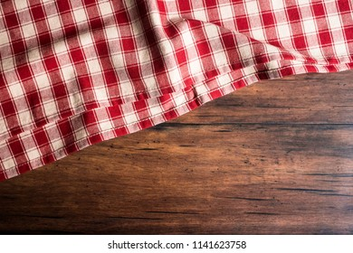 Checkered red napkin on an old wooden brown background, top view. Image with copy space. Kitchen table with a towel - top view with copy space.