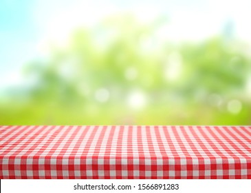Checkered red picnic table cloth on blurred natural background wmpty space.