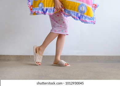 Checkered Warm Slipper. Female Standing in Pink Pajamas Pants and Shoes Holding A Pink Pillow on The Floor Background Great For Any Use.