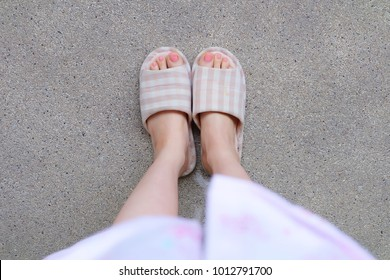 Checkered Warm Slipper with Pink Manicure Nails. Female Legs and Feet in Pink Pajamas and Slippers on The Cement Background Great For Any Use.