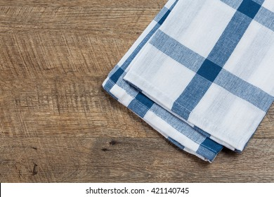 Checkered white blue kitchen towel on walnut wood background. Horizontal image, top view with copy space.
